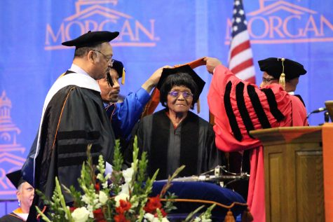 Authorine Foster receiving her honorary  Doctorate degree from President David Wilson as Reverend Jesse Jackson looks on. Photo by Benjamin McKnight III