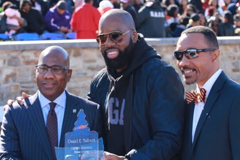 "Morgan alum and producer of ""Almost Christmas"" David Talbert (center) along with campus president David Wilson (left) and Kweisi Mfume (right) at halftime of Saturday"