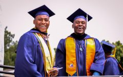 Graduates pose side-by-side in their cap and gown in 2019's Spring Commencement Ceremony.