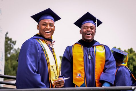 Graduates pose side-by-side in their cap and gown in 2019