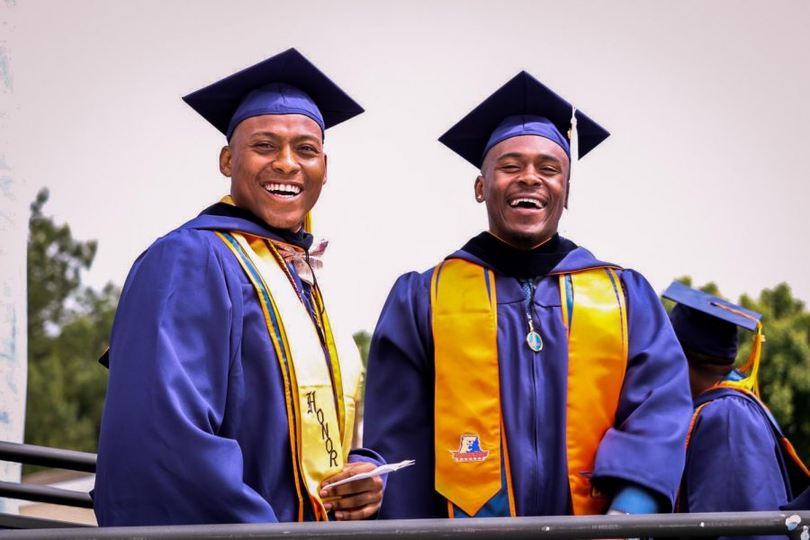Graduates+pose+side-by-side+in+their+cap+and+gown+in+2019%27s+Spring+Commencement+Ceremony.
