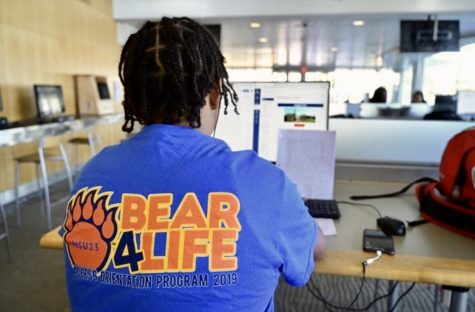 A Morgan student utilizes an Earl S. Richardson Library computer while wearing a 2019 ACESS Orientation Program shirt.