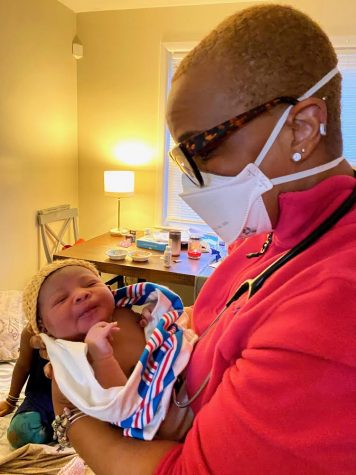 A masked Nikki Christian-Genius holds a baby in her arms after completing a home birth.